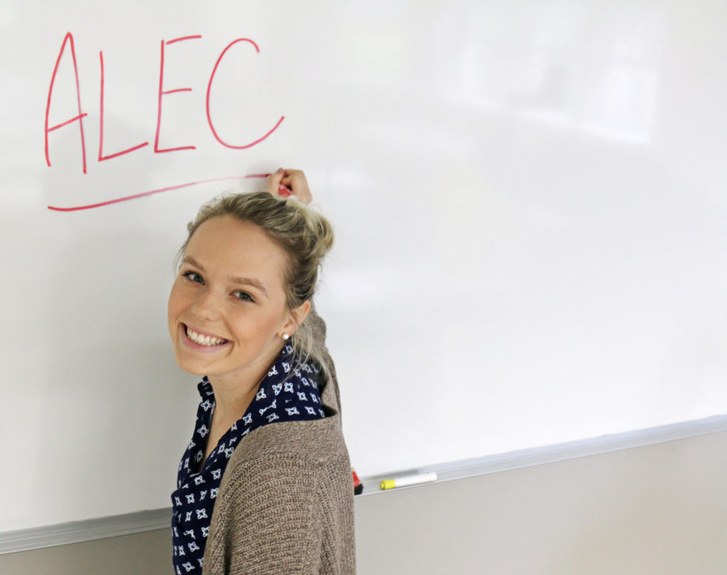 Woman writing ALEC on whiteboard