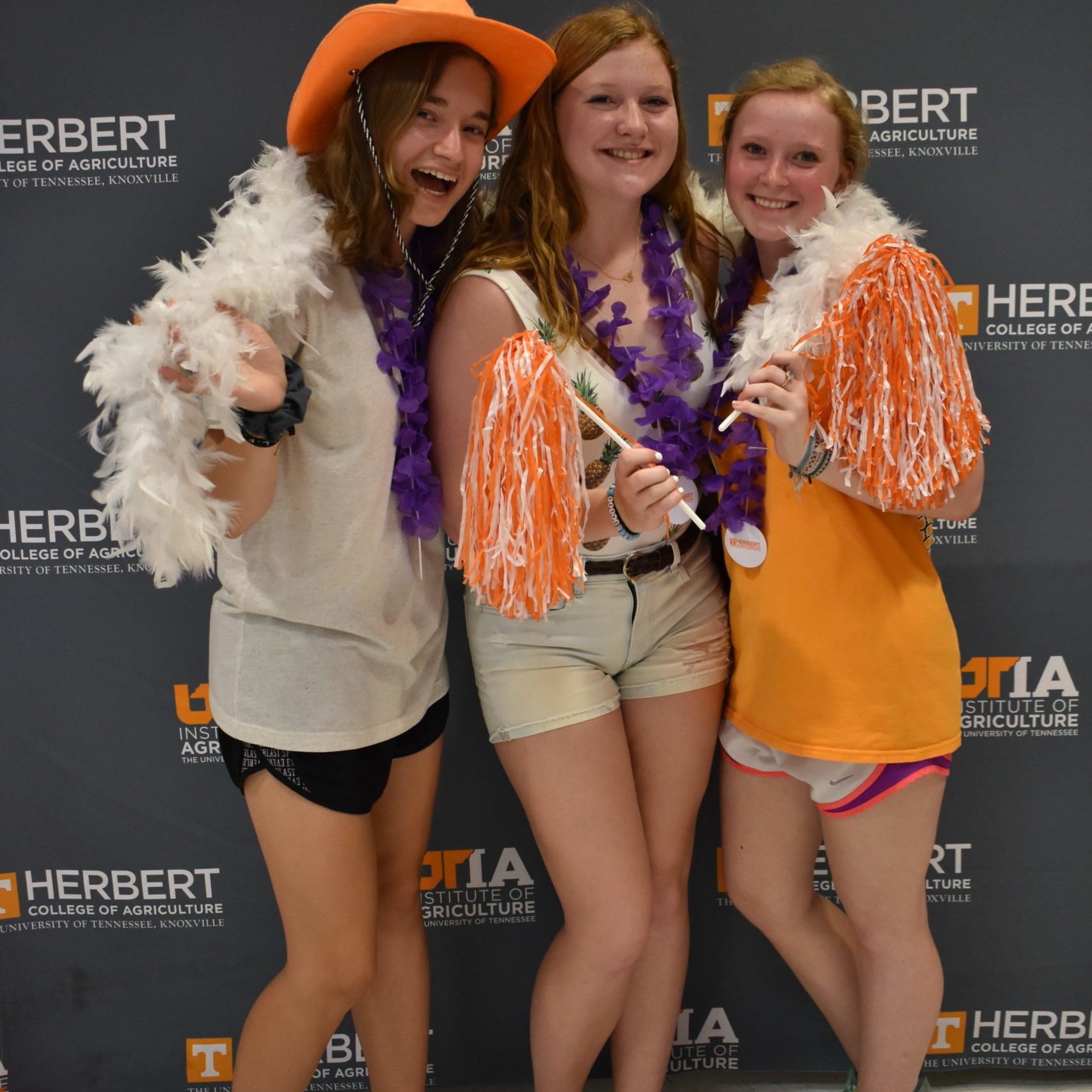 Students dressed in orange and white in front of Herbert College of Agriculture backdrop