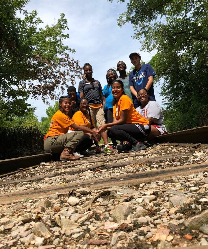 Group of students pose on railroad tracks