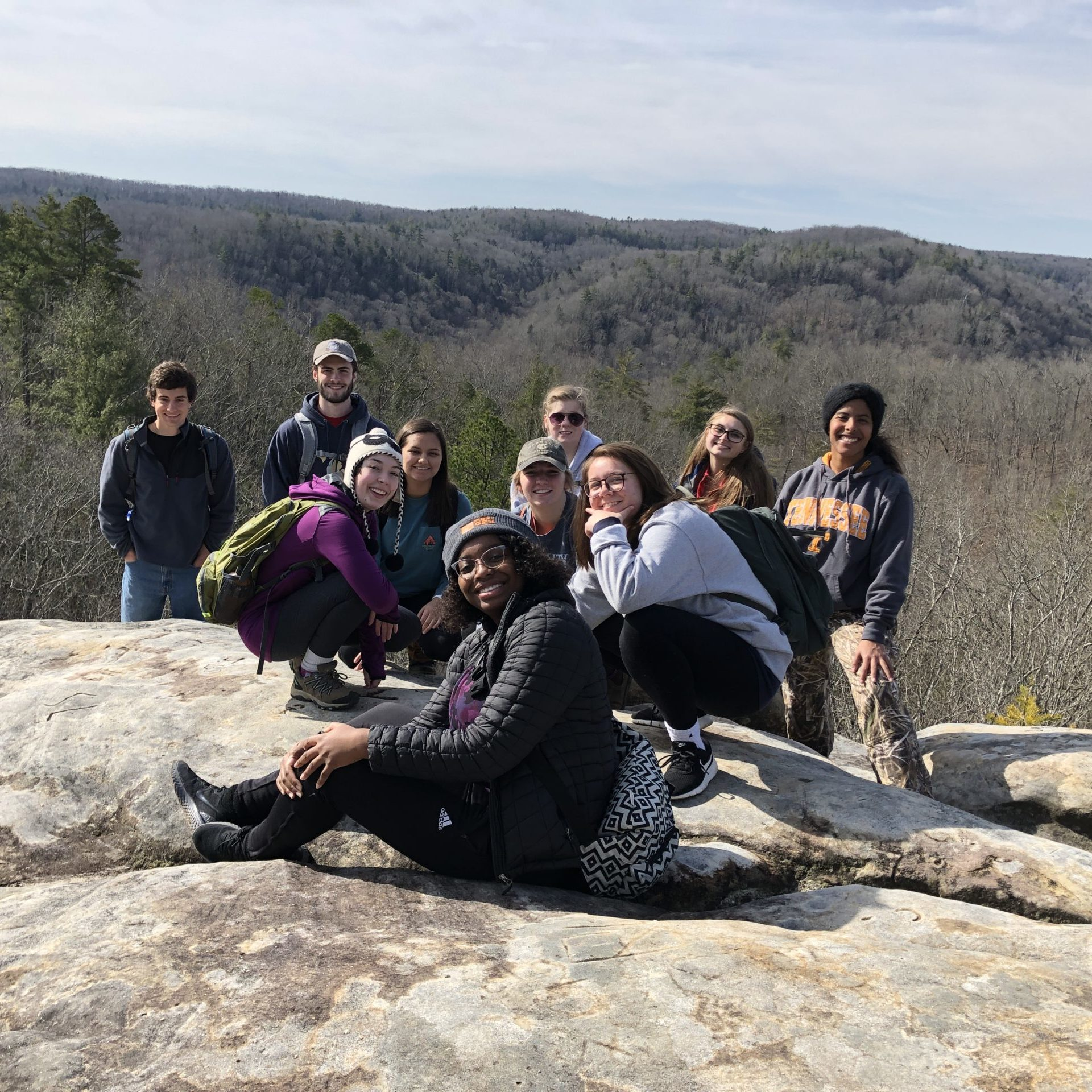 Students pose on a rock